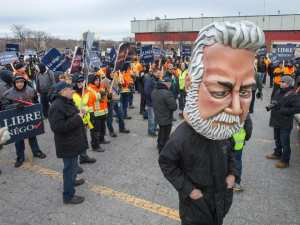 a man wearing a giant head in the likeness of Quebec Premier Philippe Couillard attends a protest against public sector cuts.
